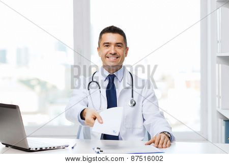 medicine, profession, technology and people concept - happy male doctor with prescription and laptop computer in medical office