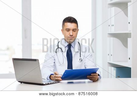medicine, profession, technology and people concept - male doctor with clipboard and laptop computer in medical office