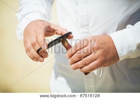 Man Cutting A Cigar