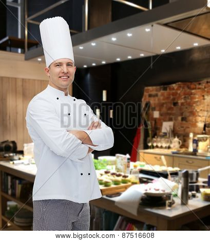 cooking, profession and people concept - happy male chef cook with crossed hands over restaurant kitchen