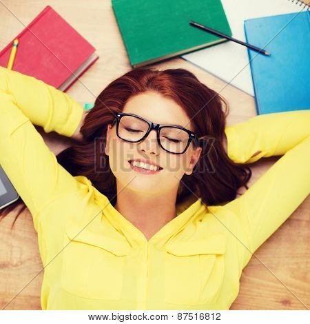 education and home concept - smiling redhead female student in eyeglasses lying on floor with closed eyes