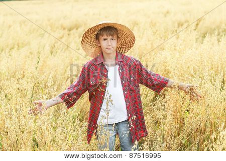 Portrait Of Walking Teenage Boy In Yellow Wide-brimmed Natural Straw Hat