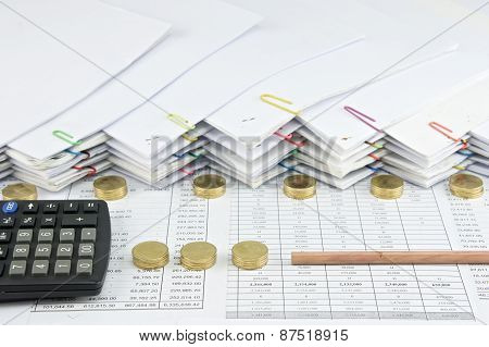 Bottom Of Pencil With Calculator Between Pile Of Gold Coins