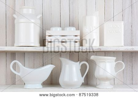 Two rustic white wood kitchen shelves with all white accessories. Items include, Salt and pepper shakers, pitchers, gravy boat and ceramic milk can. Horizontal format.