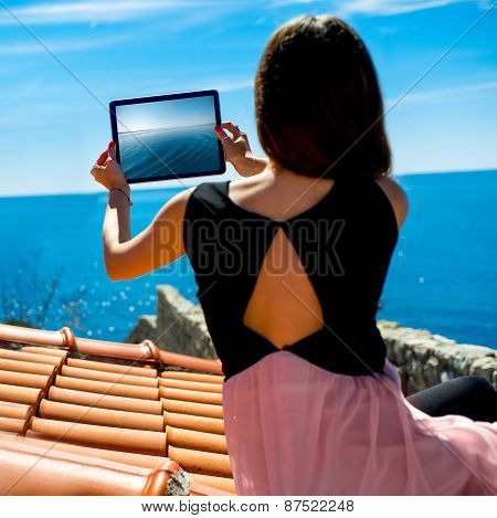 Woman traveler photographing sea scape