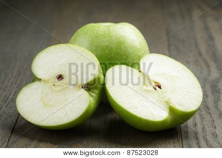 green sour apple on wood table sliced