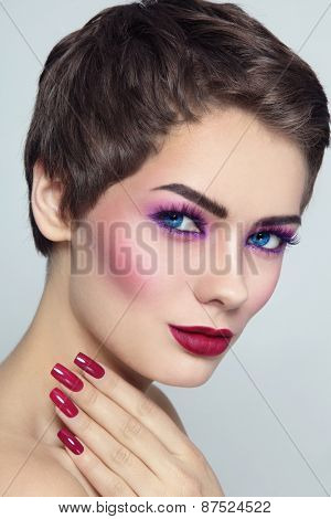 Portrait of young beautiful woman with fancy make-up and manicure