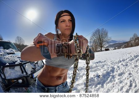 young athletic woman pulling car in winter