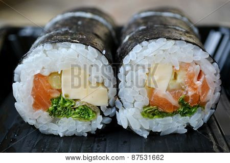Delicious rolls and sushi with salad, salmon and philadelphia