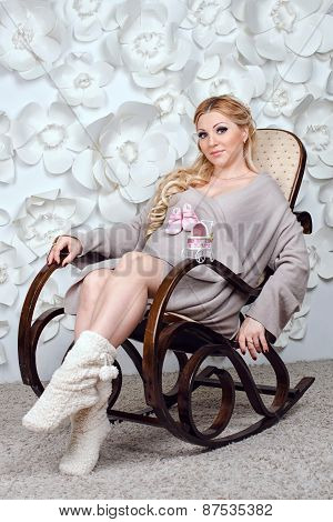 Pregnant woman on chair on white background with flowers.