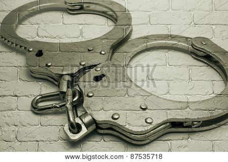 Handcuffs On Background Of Gray Brick Wall