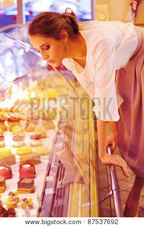 Woman Choosing Cakes And Desserts In A Cafe