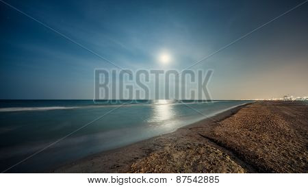 Beautiful night seascape of a sand beach with full moon