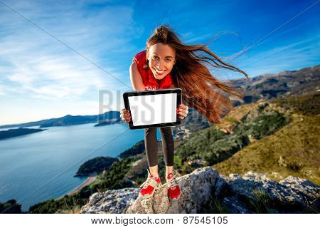 Sports woman with digital tablet on the mountain