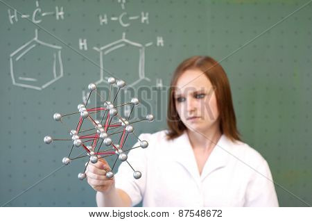 Woman Analyzing Molecule Model In Front Of Class