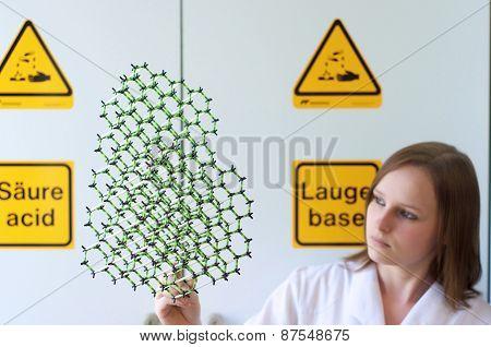 Woman Looks Into A Molecule Model