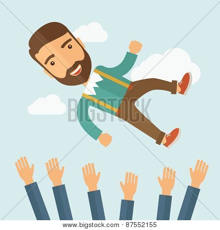 A successful smiling hipster being thrown in air.