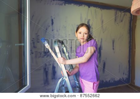 Little girl sitting on step ladder. Renovation concept.