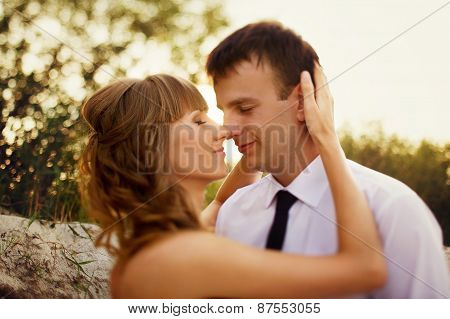 Portrait Of Bride And Groom Kissing On The Background Of Rays Of Light