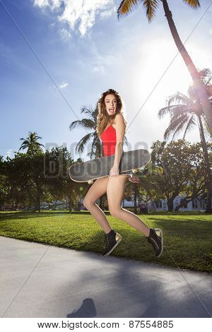 Young woman jumping with a longboard. Backlight with palm trees.