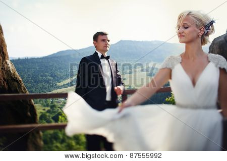 Bride Waving Dress In A Landscape Mountain And Groom Standing Leaning On Fence