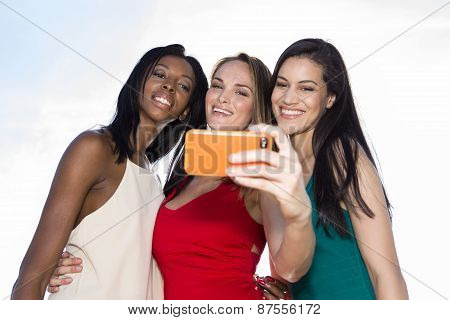 Portrait of three women taking selfies with a smartphone. Three friends posing for selfie, outdoors
