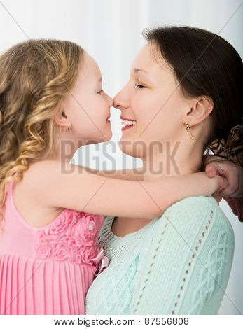 Mother and daughter touching with noses