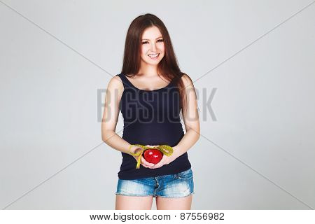 Pregnant woman with apple and measuring tape