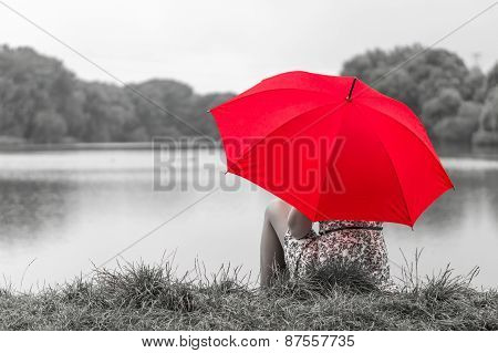 Girl With Red Umbrella Sits Near The Pond