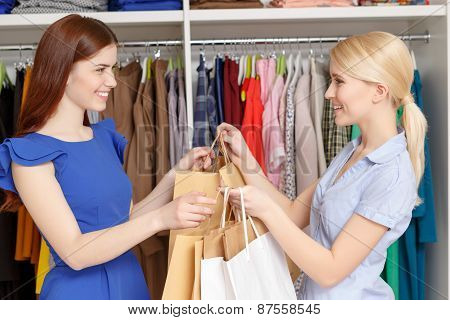 Sales assistant gives bags to the customer