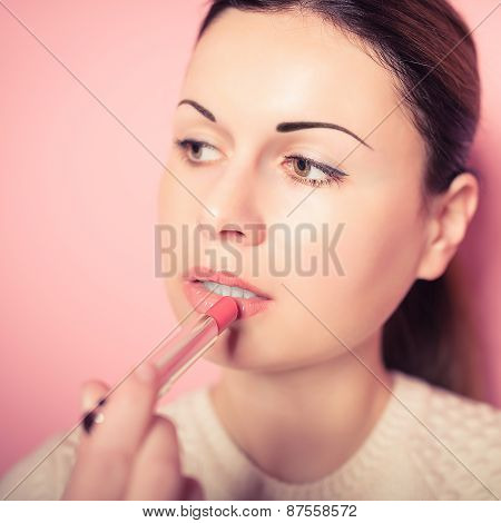 Beautiful Young Woman Makes Up Lips