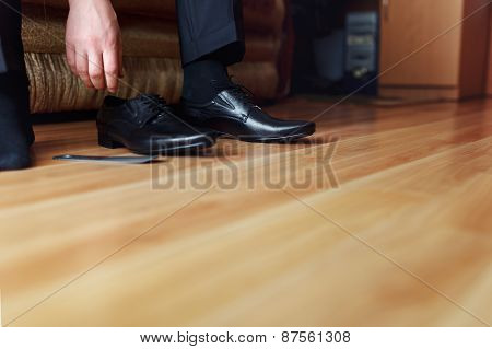 Groom Putting On Black Shoes At Home