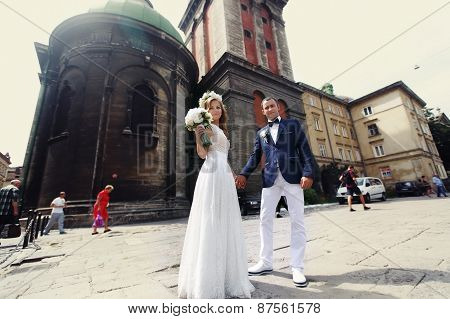 The Bride And Groom With A Bouquet Of White Roses And Wreath On A Background Of The City