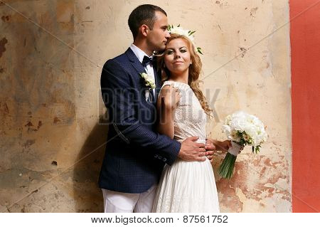 Bride And Groom Kissing On The Background Wall