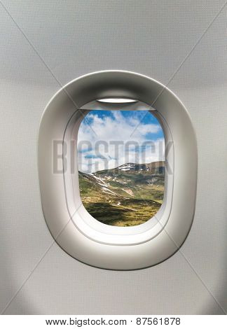 Looking Out The Window Of A Plane At The Mountains