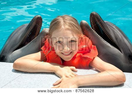 Happy Little Girl Smiling With Two Dolphins In Swimming Pool