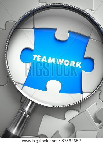 Teamwork - Missing Puzzle Piece through Magnifier.