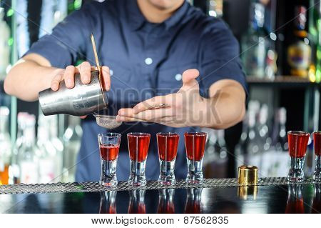 Barman makes shots in a bar