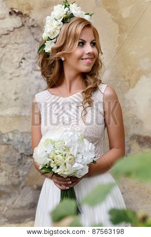 Portrait Of The Bride With A Bouquet And A Wreath Of White Roses