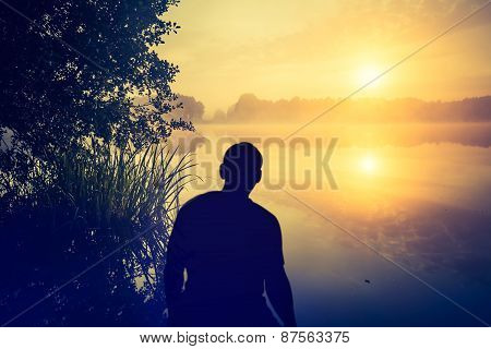 Man Watching A Sunrise Over Lake. Human Silhouette.
