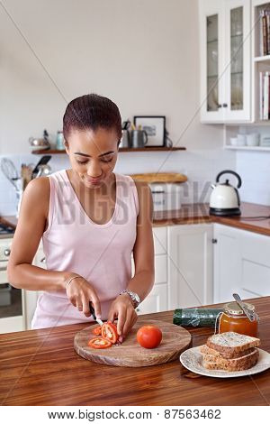 young woman making tomato sandwich kitchen at home