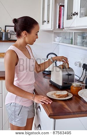 young woman making breakfast toast bread with toaster at home kitchen