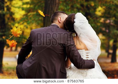 Wedding Couple Sitting On A Bench In Autumn Park