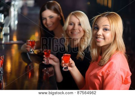 Three women have a drink in the bar