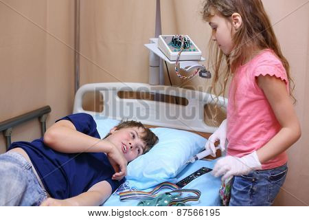 Girl standing with a syringe in hand near the boy lying on the bed in a hospital ward