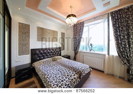 Interior modern bedroom in the Greek style with leopard print on the walls and bed