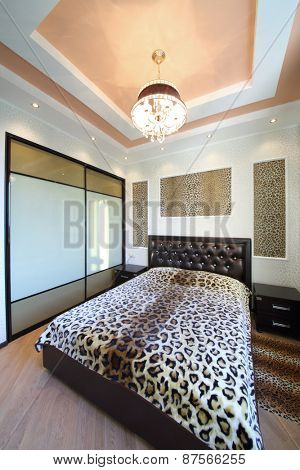 Modern bedroom in the Greek style with leopard print on the walls and bed