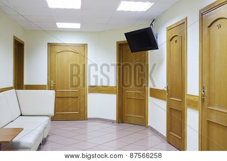 Interior of waiting area with five doors and a white sofa in the medical center hospitals