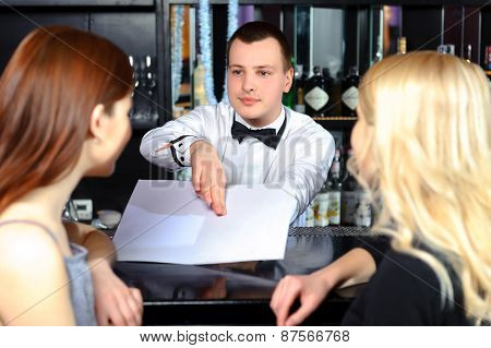 Women and barman by the counter