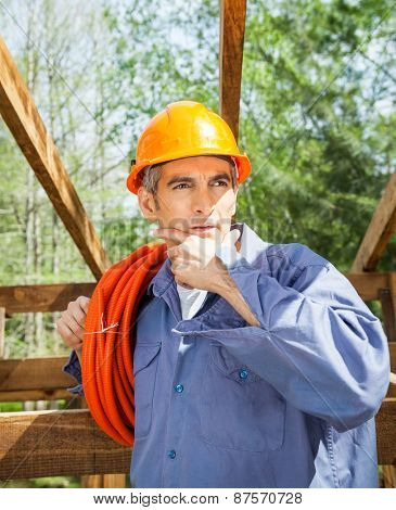 Thoughtful male construction worker with hand on chin looking away at site